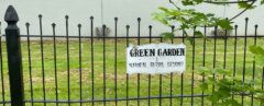 "wrought iron fence with sign that reads, ""Green Garden natural burial ground"""