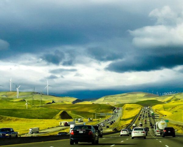 A road full of cars, surrounded by rolling green hills.