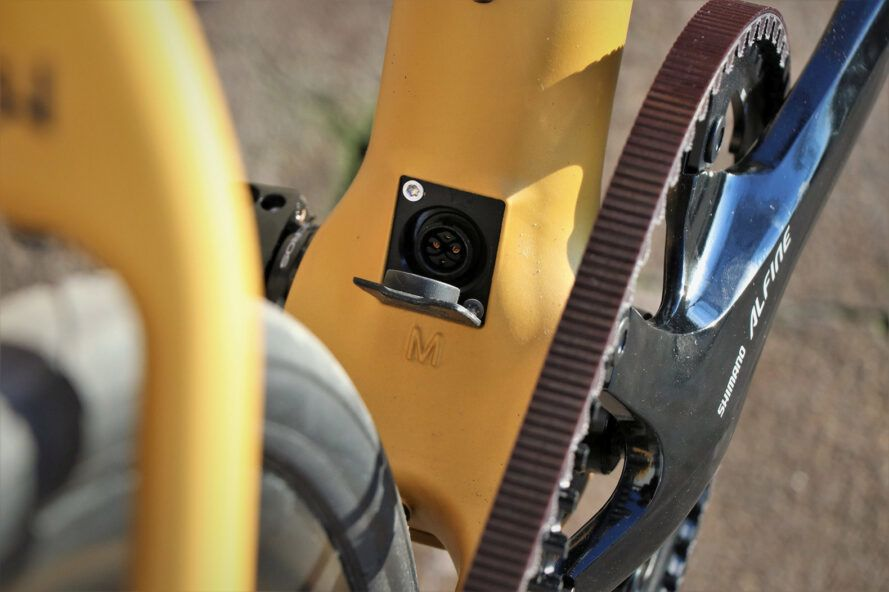 A close-up of an electric plug at the front of a yellow bike.