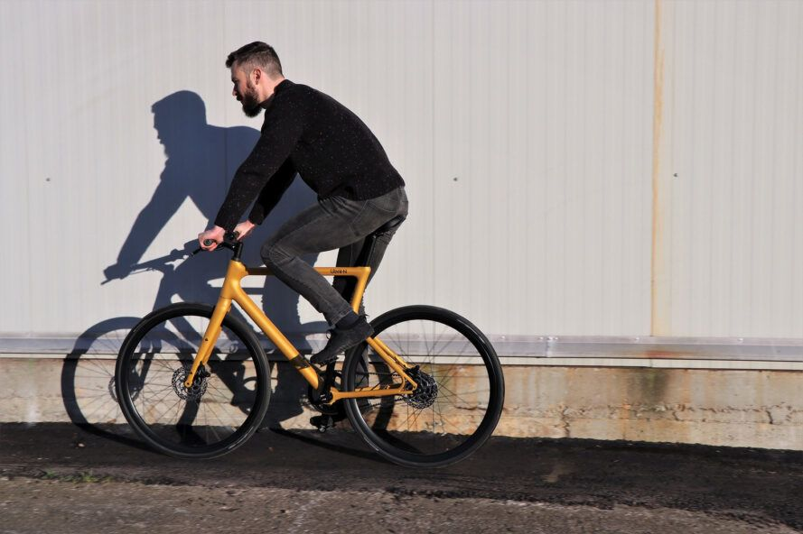 A person riding a yellow bicycle, heading to the left.