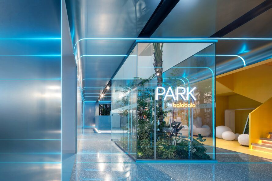 A PARK by balabala sign in neon blue and yellow, against a glass wall encasing green plants.