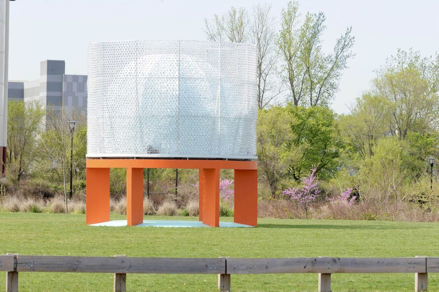 A green lawn with a pavilion-like structure built in the middle. The structure has an orange base and white top.