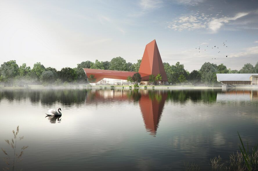 Two red, angular volumes making up a building by a serene lake.