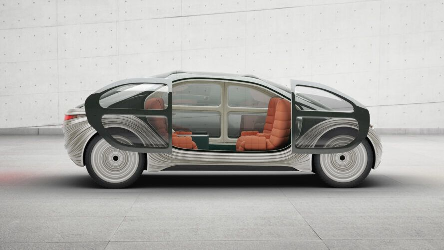 gray electric car with sliding doors that are open to reveal orange interior