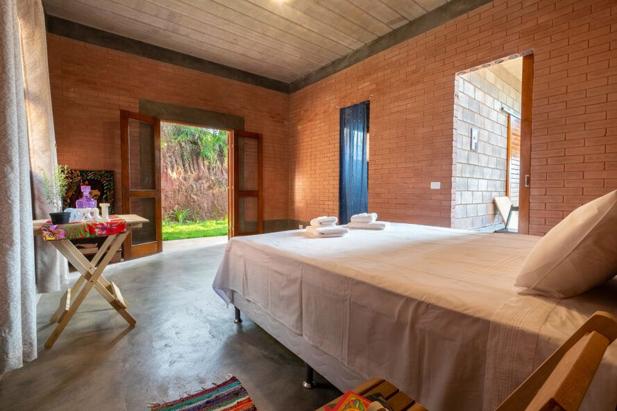 white bed in room with rammed earth walls