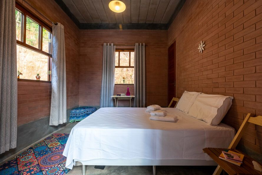 white bed in room with rammed earth walls and tall windows
