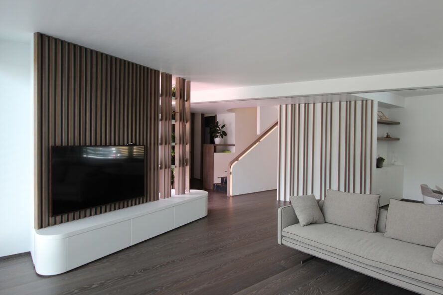 white sofa near wood wall with mounted TV