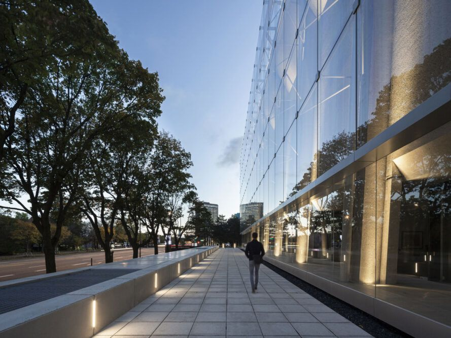 person walking along path next to glass building at dusk