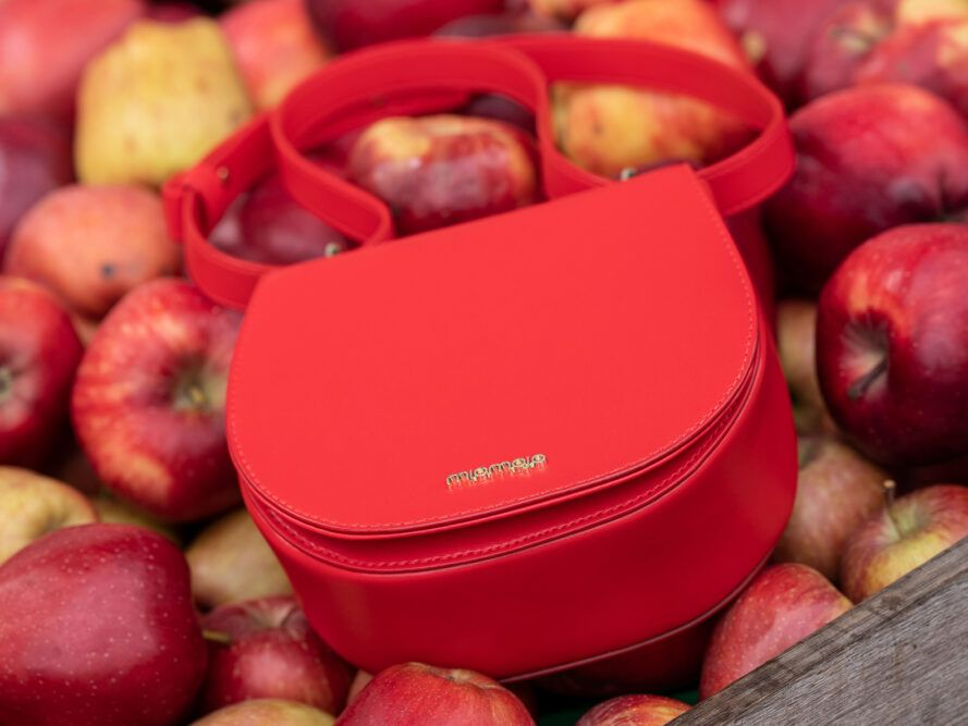 red vegan leather purse on pile of apples