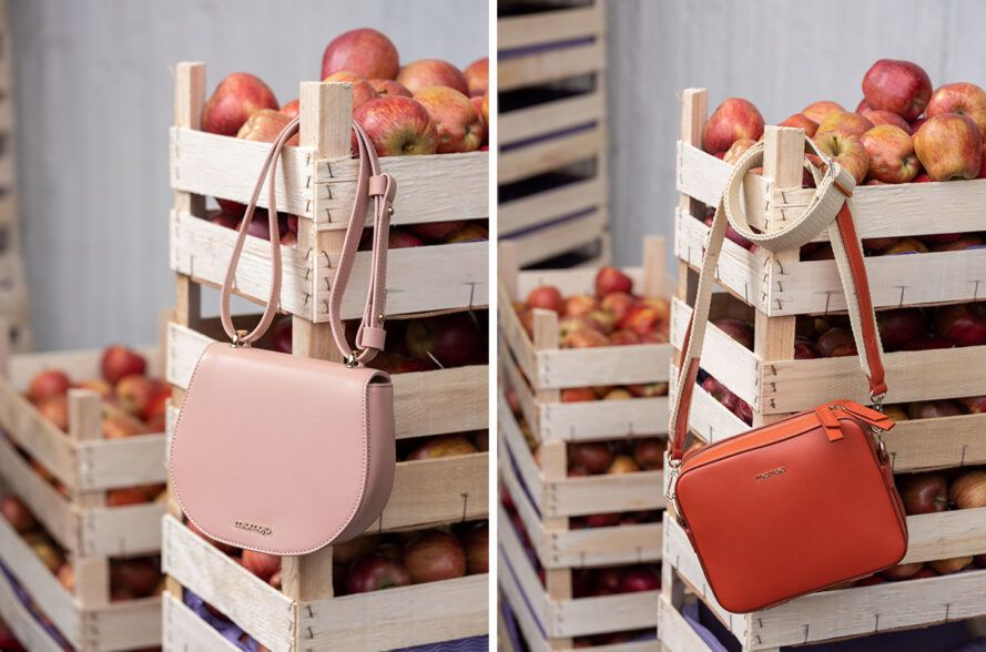 pink and orange handbags hanging from apple crates