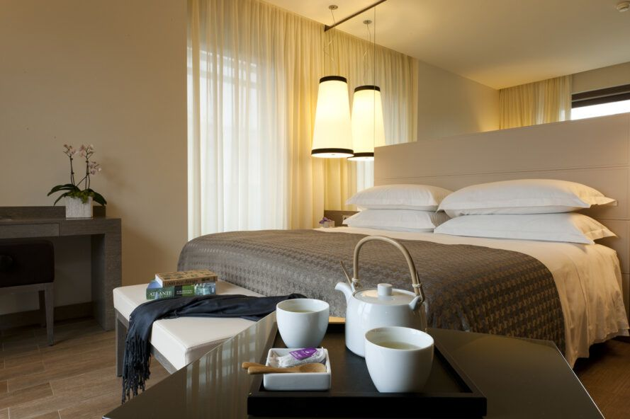 A hotel room with a bed in gray and white linens.