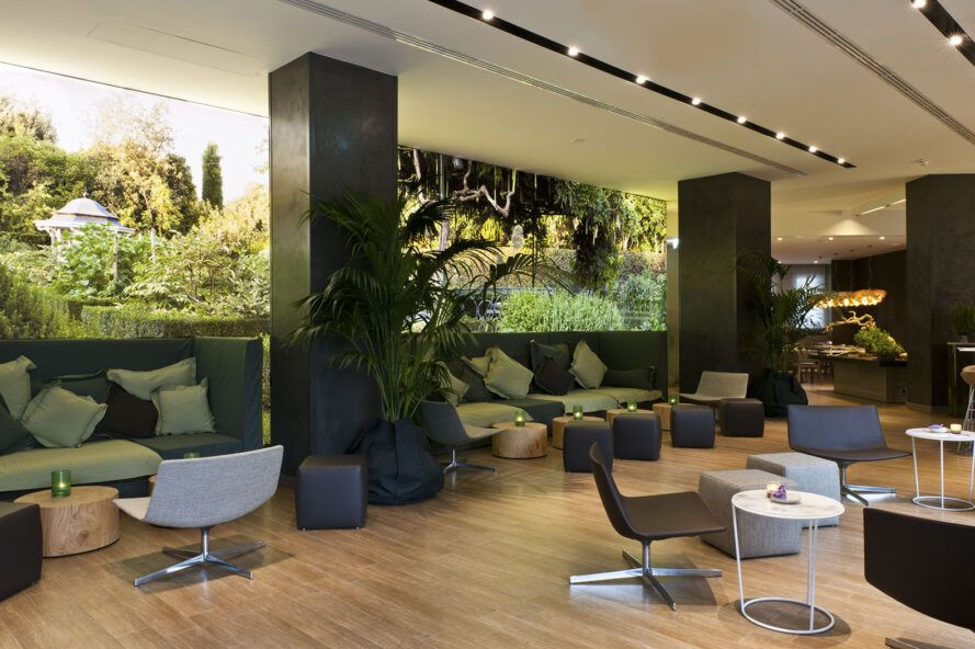 A green hotel lobby with chairs, tables and sofas.