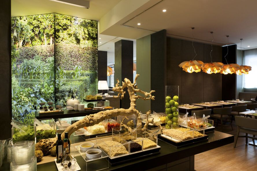 A green hotel lobby with art installations in a nature theme.