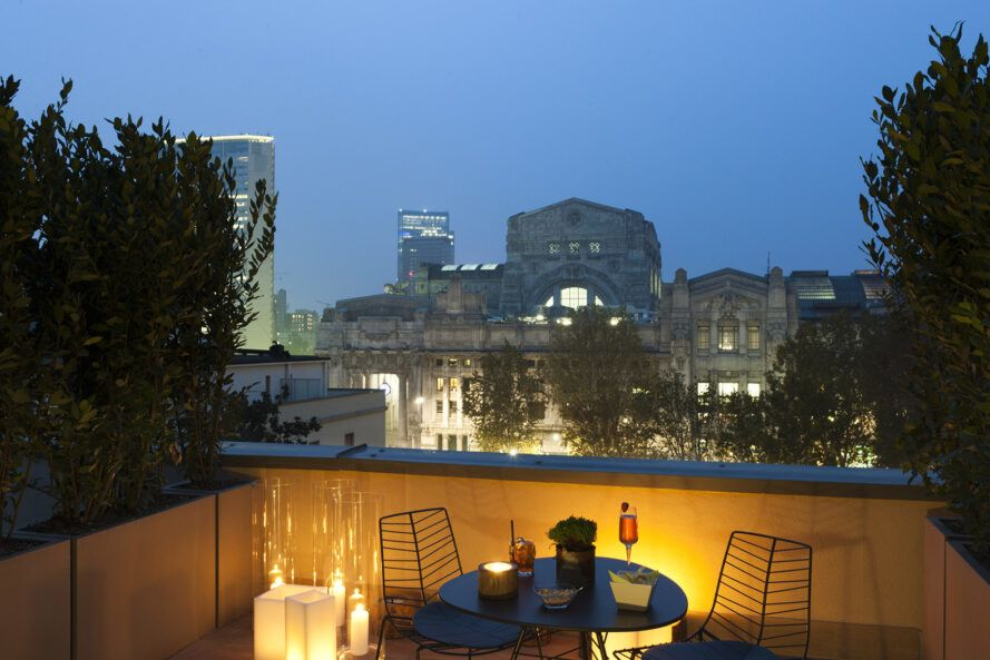 A green rooftop with a round table and two chairs that overlook Milan at night.