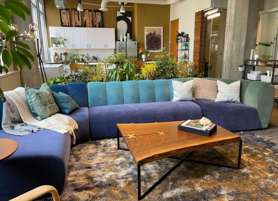 A living room with a blue sofa with a rectangular, wood coffee table in front of it.