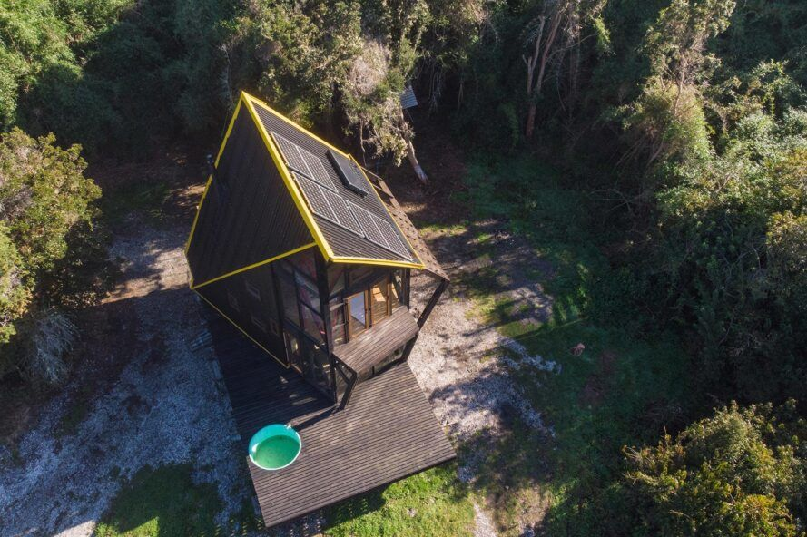 aerial view of wood cabin with hot tub on the deck