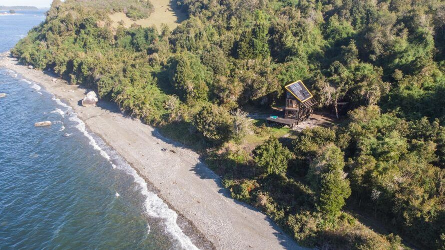 aerial view of cabin in forest just steps from a beach