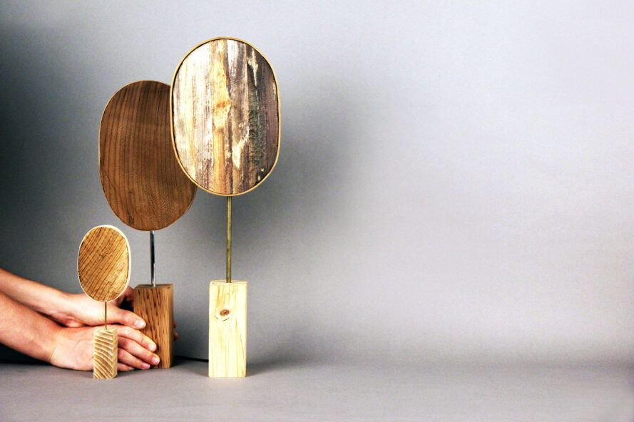 person arranging round lamps made from banana fibers