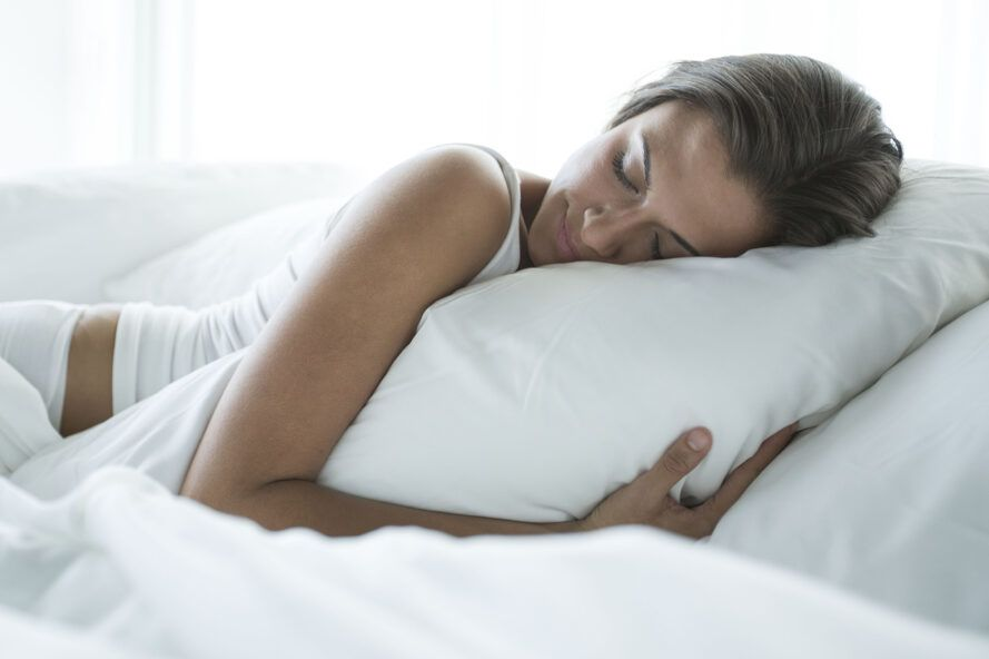 A person is sleeping on the bed, holding a pillow.