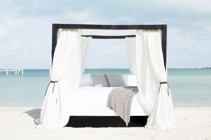 A four-poster bed with white linens, gray pillows and a gray blanket on the beach.