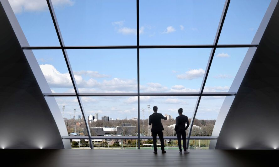 rendering of people looking out slanted glass wall