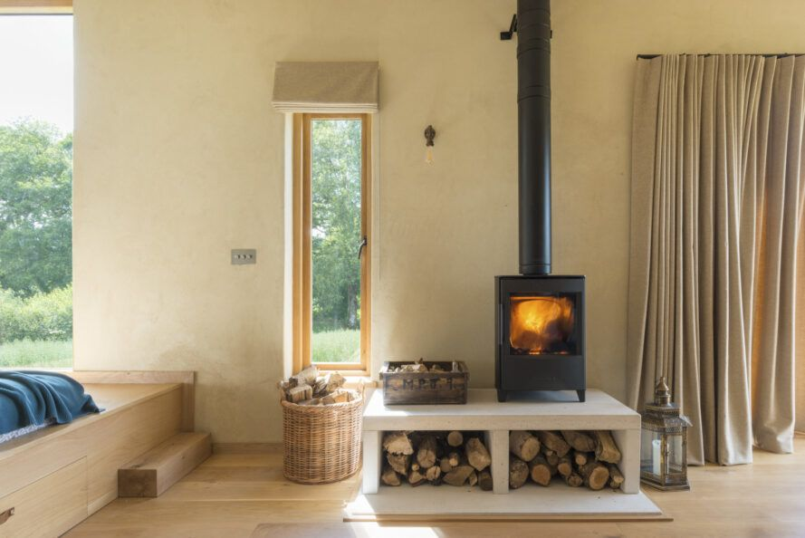 Wood burning stove on wooden platform in wooden house