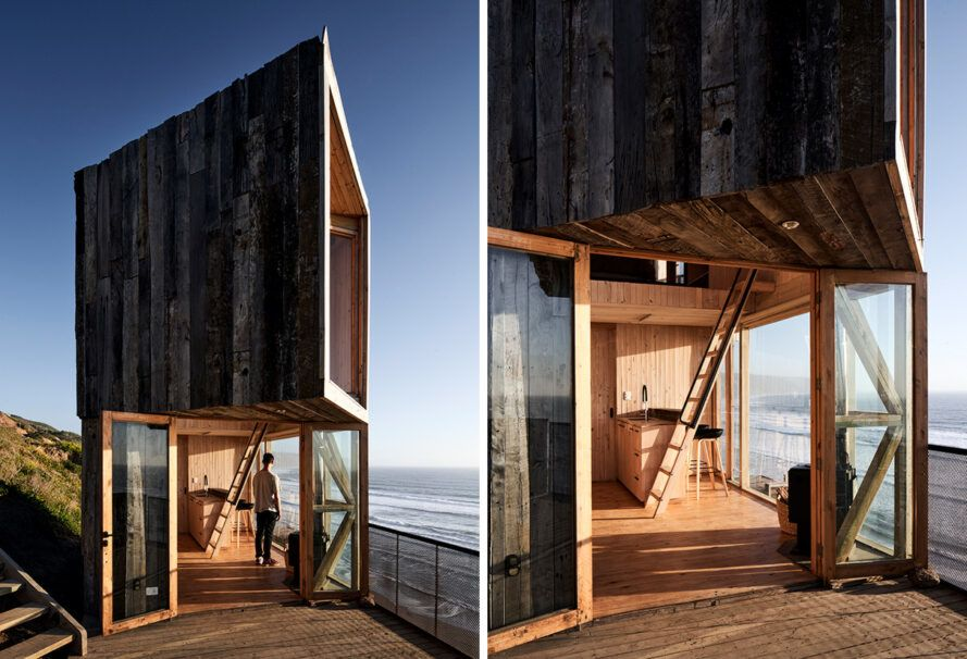 An angular wooden house with a glass wall at the bottom