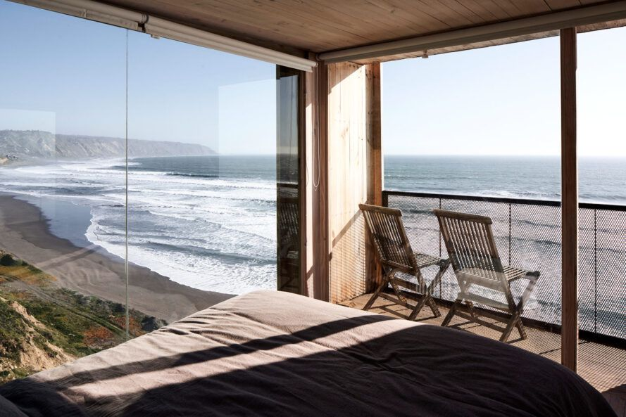 Grey bed facing the glass wall, overlooking the sea