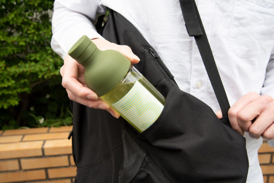 person putting green tea bottle in backpack