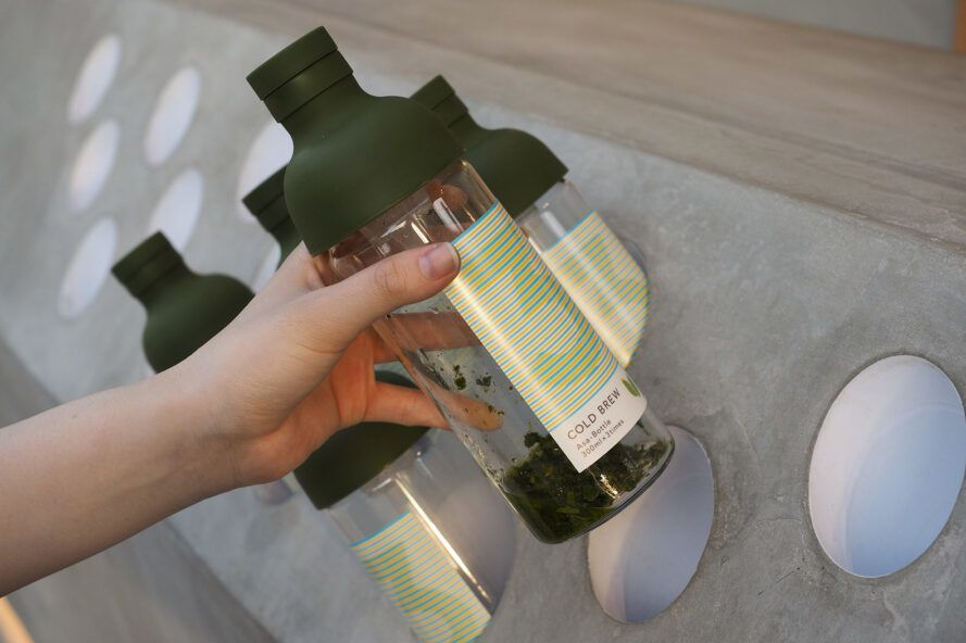 person pulling bottle of tea leaves from counter