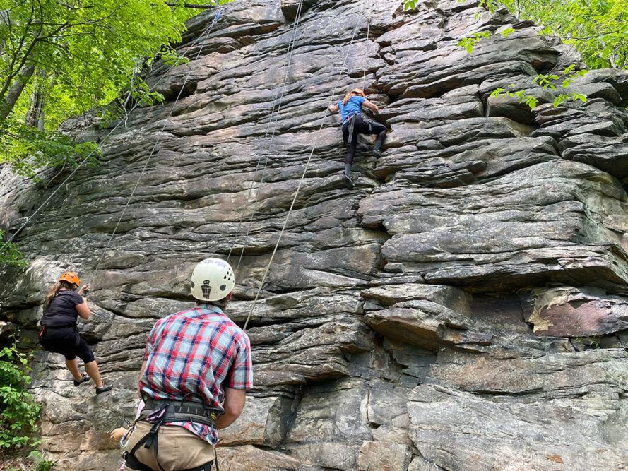 people climbing a rock wall in forest