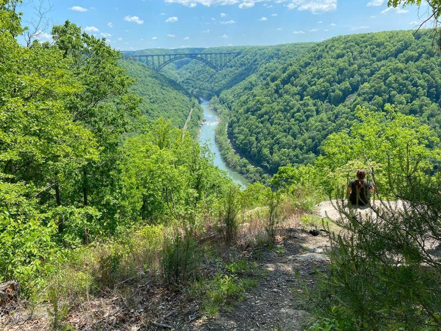 person sitting on rock overlooking New River Gorge