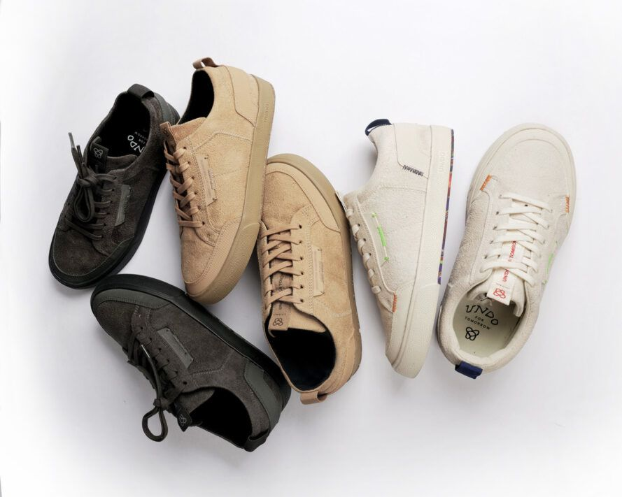 White, black, gray and tan vegan sneakers on a white background