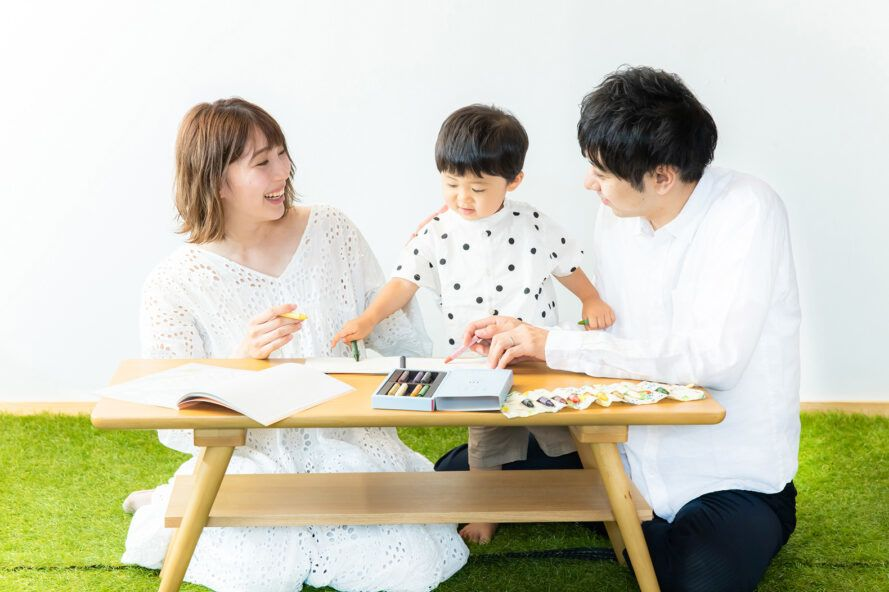 family drawing together with box of crayons