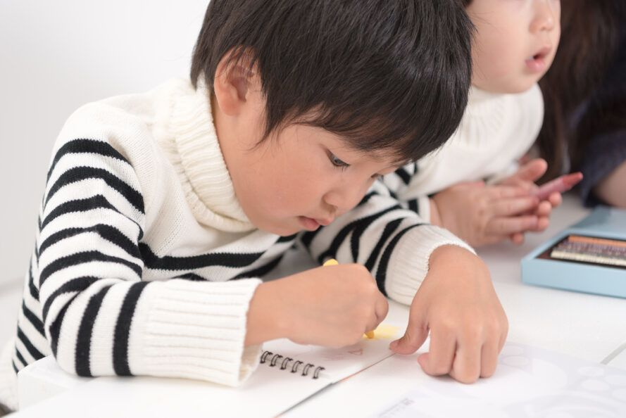 child drawing with yellow plant-based crayon