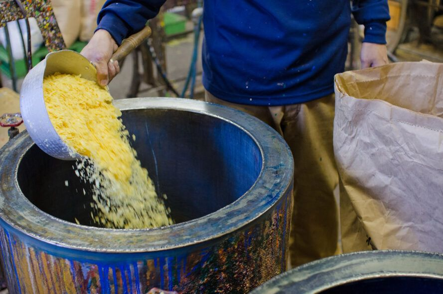 person pouring rice wax into blue vat