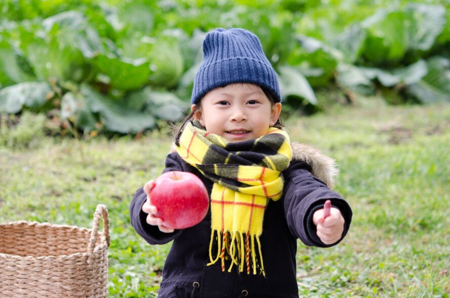 child holding apple in one hand and red crayon in other hand
