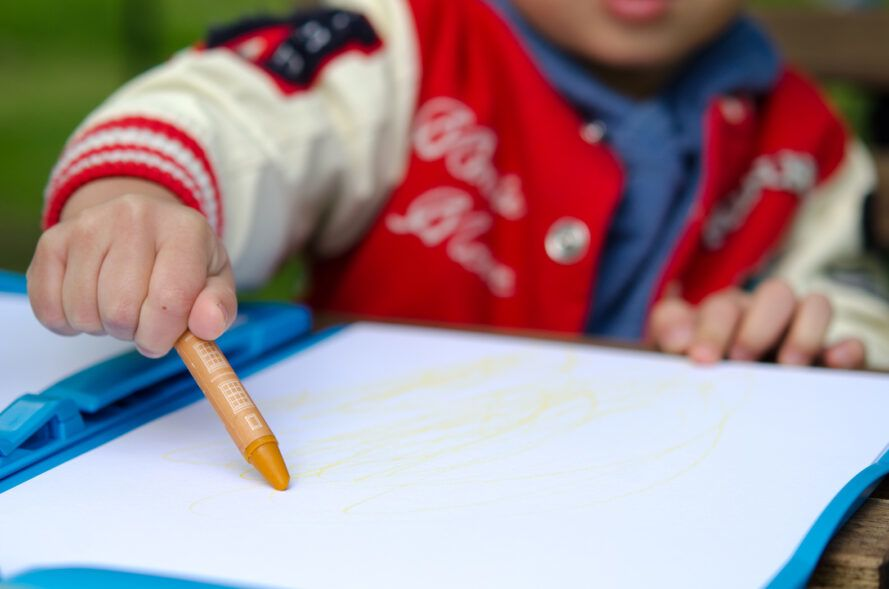 kid drawing on paper with orange crayon