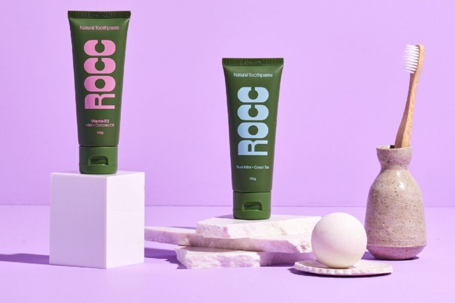green toothpaste tubes on light purple background
