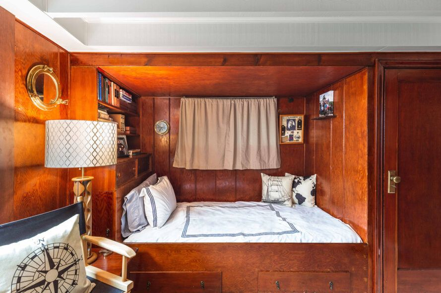 bedroom with wood walls and bed nook built into wall