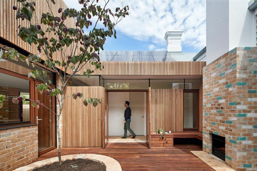 Wood and brick house with wooden doors leading to the terrace