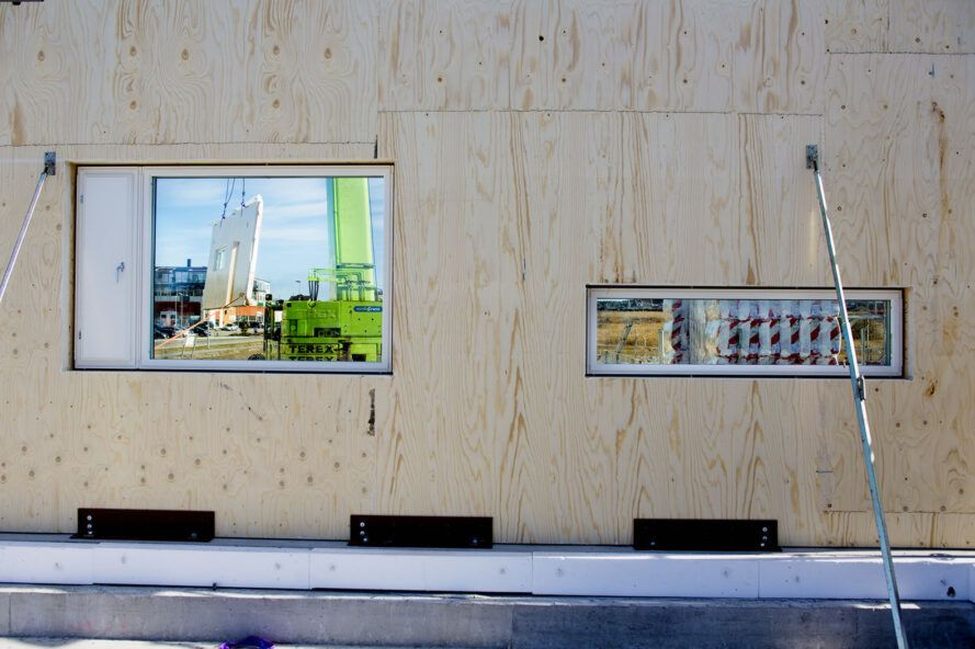 A wooden wall with window holes is being built.