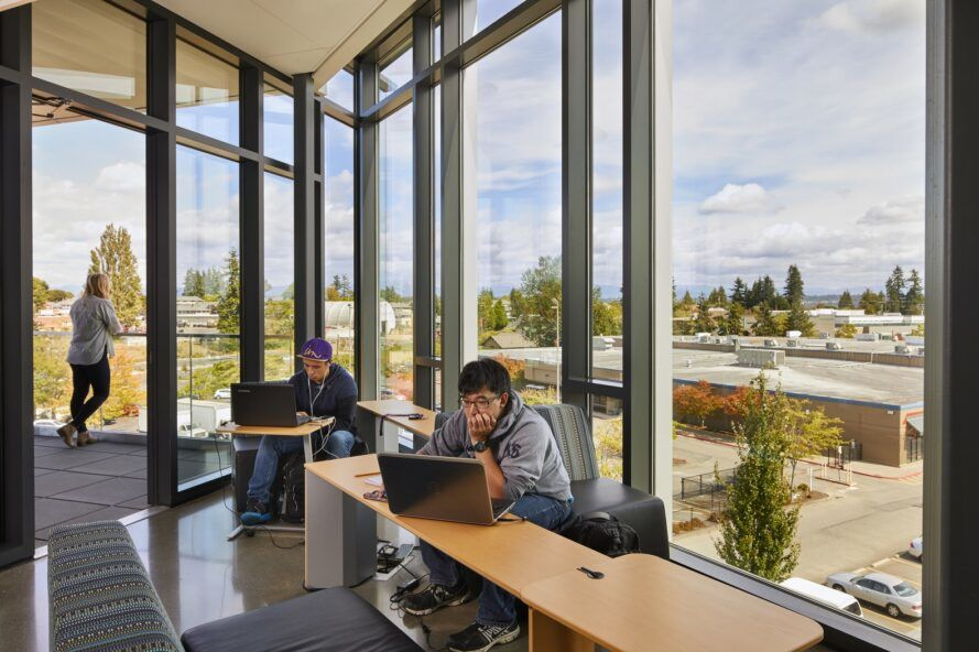 A space where students sit to study, surrounded by large bay windows.