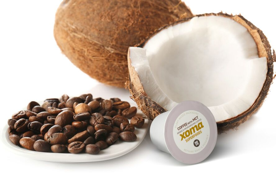 plant-based coffee pods next to coffee beans and coconut