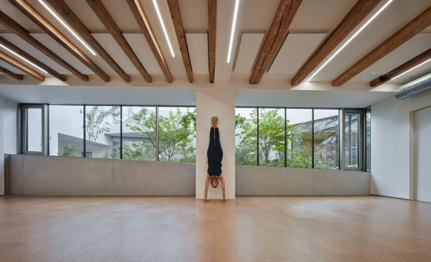 Man doing handstand in large white room with wood beam ceiling