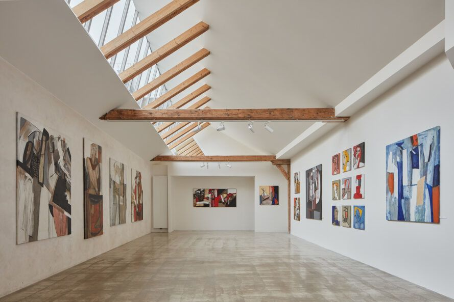 White room with wooden beams and artwork on the walls