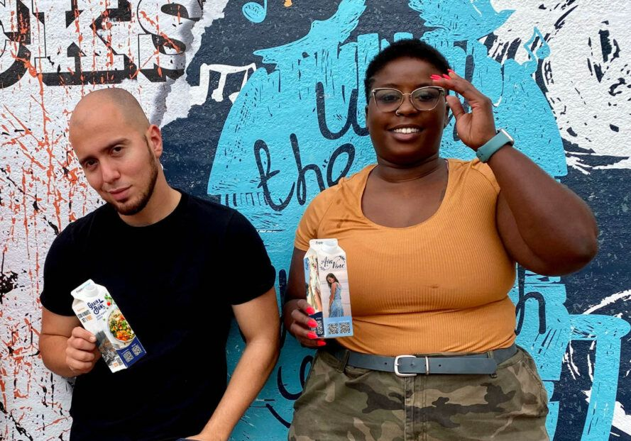 Two people standing against a wall holding cartons of FreeWater.