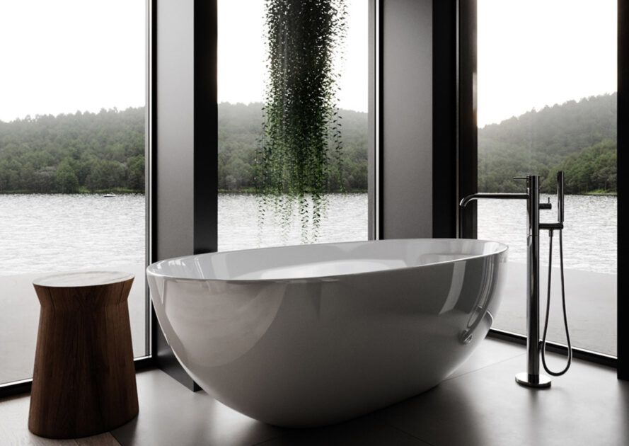 A white free-standing bathtub in a room of glass walls, with a green plant hanging overhead.