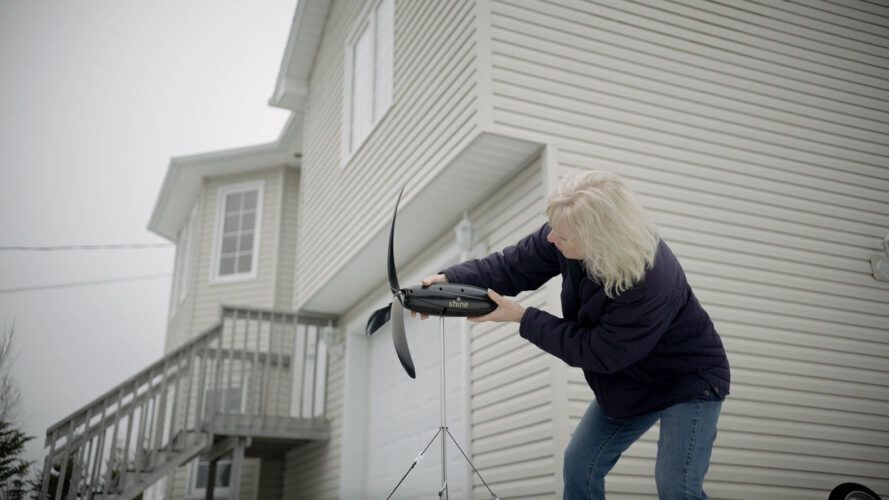a person who assembles a portable wind turbine outside the house