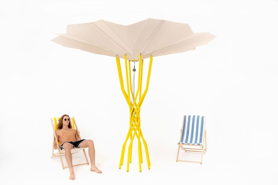 People sitting on beach chairs under yellow and tan solar beach umbrellas